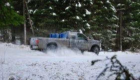 camion 4x4 che va alla deriva sulla strada della neve di inverno in foresta Fotografia Stock Libera da Diritti