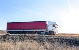 Camion con i giri del contenitore sulla strada principale Fotografia Stock