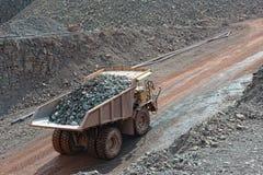 Camion de déchargeur avec les pierres chargées conduisant le long dans un quary exploitation image libre de droits