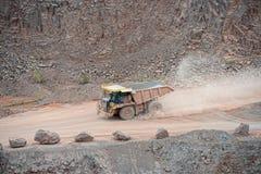 Camion de déchargeur conduisant autour dans une carrière de mine de porphyre photographie stock libre de droits