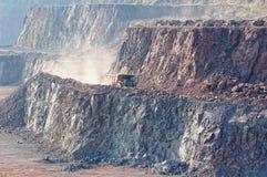 Camion de déchargeur conduisant par une mine de carrière excavatrice dans le backgro photographie stock
