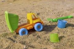 Camion de déchargeur jaune de jouet en sable sur la plage avec la remorque verte de verseur et les roues bleues image libre de droits