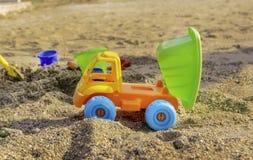 Camion de déchargeur jaune de jouet en sable sur la plage avec la remorque verte de verseur et les roues bleues photographie stock libre de droits