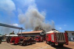 Camion de pompiers et entrepôts brûlants avec de la fumée noire contre le bleu Image libre de droits