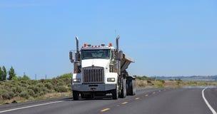 Camion dei semi con il rimorchio che guida sulla strada principale Immagini Stock