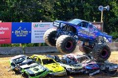 Camion di mostro di evoluzione di Overkilll che salta sopra le automobili immagini stock libere da diritti