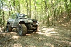 Camion di mostro gran-a ruote fuori strada nella foresta del fango Fotografia Stock