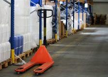 Camion di pallet arancio per il pacchetto nel magazzino Immagini Stock