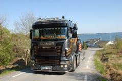 Camion di Scania che scala collina con il lago nei precedenti Fotografia Stock