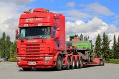 Camion di Scania 164G 480 che trasporta la macchina di maneggio del materiale Fotografie Stock