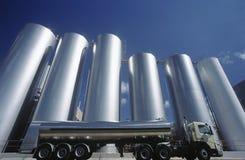 Camion di trasporto del latte parcheggiato accanto ai serbatoi Fotografia Stock