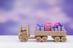 Camion en bois de jouet avec des cadeaux dans des boîtes décorées des rubans et des arcs en papier élégant photos libres de droits