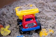 Camion en plastique de jouet dans le sable Image stock