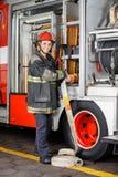 Camion felice di Adjusting Hose In del pompiere immagine stock libera da diritti