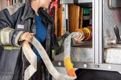Camion femminile di Adjusting Hose In del pompiere immagine stock libera da diritti