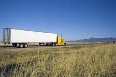 Camion giallo che guida verso le montagne. immagini stock libere da diritti