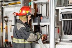 Camion maschio di Adjusting Hose In del pompiere fotografia stock libera da diritti
