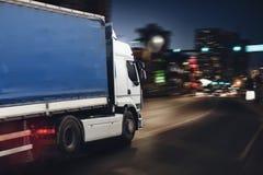 Camion rapide sur une route urbaine livrant la nuit Photographie stock