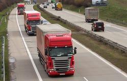 Camion rossi che guidano sulla strada principale Immagine Stock Libera da Diritti