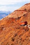 Camion rosso che guida su una strada della montagna su crepuscolo di inverno, sul paesaggio fantastico della cresta rossa della m fotografia stock libera da diritti