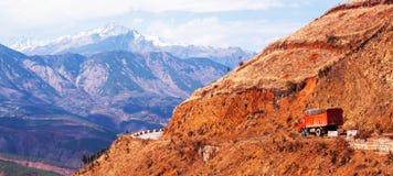 Camion rosso che guida su una strada della montagna su crepuscolo di inverno, sul paesaggio fantastico della cresta rossa della m immagini stock libere da diritti