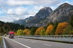 Camion rosso che guida sulla strada principale nelle alpi Immagini Stock Libere da Diritti
