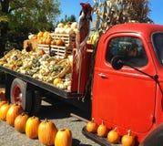 Camion rosso d'annata dell'azienda agricola con le zucche del raccolto di caduta Fotografie Stock Libere da Diritti