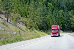 Camion rosso moderno dei semi con il carico di movimento del rimorchio in salita su impressionante Fotografia Stock