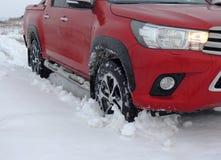 Camion rouge dans la neige profonde à l'aventure extérieure de route Images libres de droits