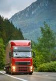 Camion rouge sur la route de montagne le soir Images libres de droits