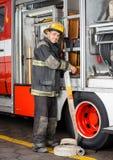 Camion sorridente di Adjusting Hose In del pompiere immagine stock