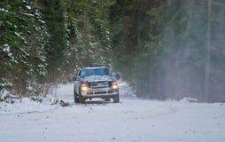 camion 4x4 sulla strada della neve di inverno in foresta Immagini Stock Libere da Diritti