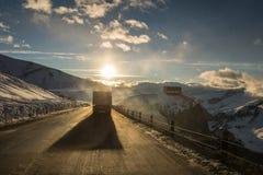 Camion sulla strada militare georgiana sul tramonto, inverno Fotografia Stock Libera da Diritti