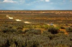 Camion sulla strada ondeggiante del deserto Immagini Stock