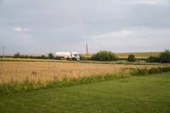 Camion sur la route se déplaçant par des champs de blé transport photos stock