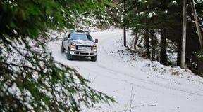 camion 4x4 che va alla deriva sulla strada della neve di inverno in foresta Immagini Stock