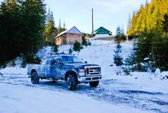 camion 4x4 sulla strada della neve di inverno in foresta davanti alle piccole case di willage Immagine Stock