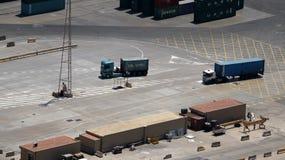 Camiones cargados del envase en un puerto Foto de archivo