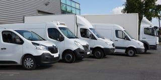 Camiones de reparto blancos parqueados en el edificio de Warehouse imagen de archivo libre de regalías
