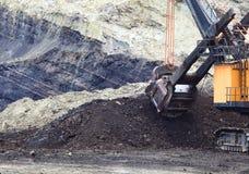 Camiones del recorrido que son cargados con el mineral Foto de archivo