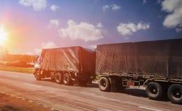camiones que apresuran en la carretera y la puesta del sol para el industr del transporte Fotos de archivo