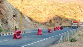 Camiones que conducen en la carretera entre las montañas a través del túnel en la India almacen de video
