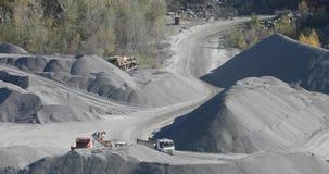 Camiones volquete industriales en una mina, el movimiento de la maquinaria pesada en una mina del granito metrajes