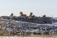 Camiones volquete que descargan la basura sobre terraplén sanitario enorme Contaminación ambiental Tecnología anticuada fotos de archivo