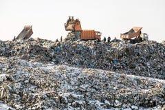 Camiones volquete que descargan la basura sobre terraplén sanitario enorme Contaminación ambiental Tecnología anticuada fotografía de archivo libre de regalías