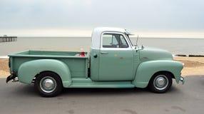 Camioneta pickup verde y blanca clásica de Chevrolet 3100 en la 'promenade' de la orilla del mar fotografía de archivo libre de regalías