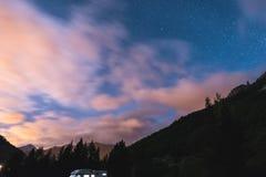 A camionete de campista sob o luar, o céu estrelado e o movimento borrado nubla-se nos cumes majestosos Atividades exteriores e a Imagens de Stock Royalty Free