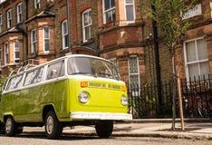 A camionete velha do verde do vintage estacionou em uma rua com casas do victorian Fotografia de Stock