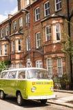A camionete velha do verde do vintage estacionou em uma rua com casas do victorian Fotografia de Stock Royalty Free