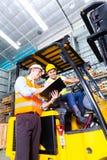 Camionista e contramestre asiáticos do elevador no armazenamento Imagens de Stock Royalty Free
